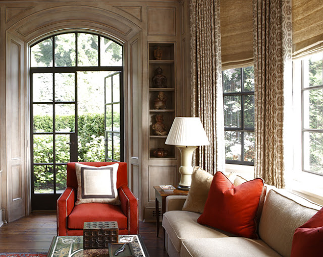 Library with light wood paneling, neutral furniture, black trimmed door, floor length curtains, a red armchair with nail head piping and red accent pillows