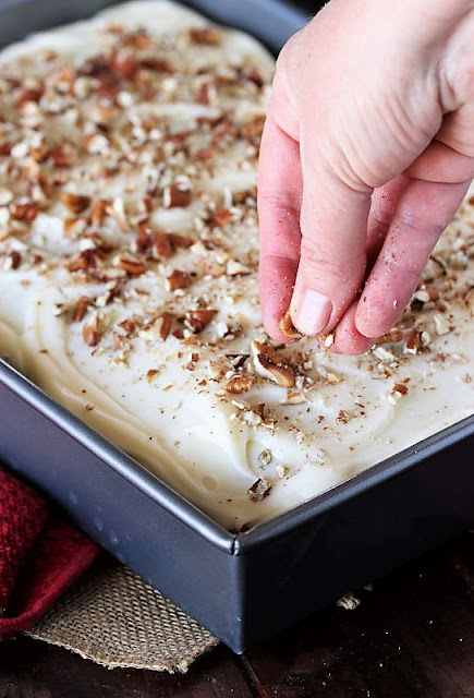 Sprinkling Carrot Cake Sheet Cake with Chopped Pecans Image