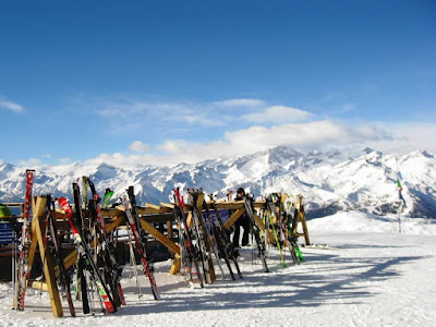 Racks of skis with a mountain and blue sky behind