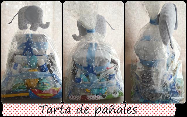 Tarta de pañales, con elefante decorativo en tela y productos de higiene para el bebé, así como baberos, toalla y bolsitas para ropa