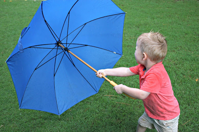 Boy playing with blue umbrella in the rain