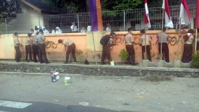 Pramuka Ngemplak Bersihkan Tembok Sekolah