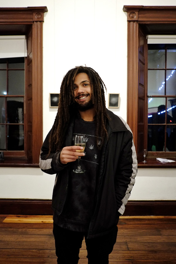 Men's style. Dreadlocks, black jacket pants, hemp motif tee shirt. Street Fashion Sydney - Photographed by Kent Johnson.