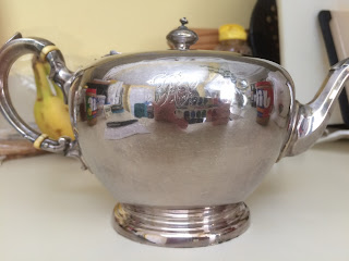 Silver teapot with reflection of kitchen including two jars of peanut butter.