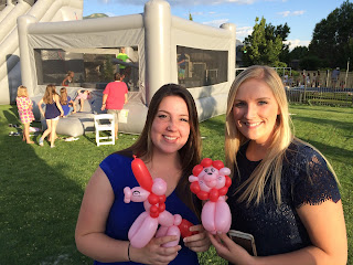 Two women posing with their balloon animals