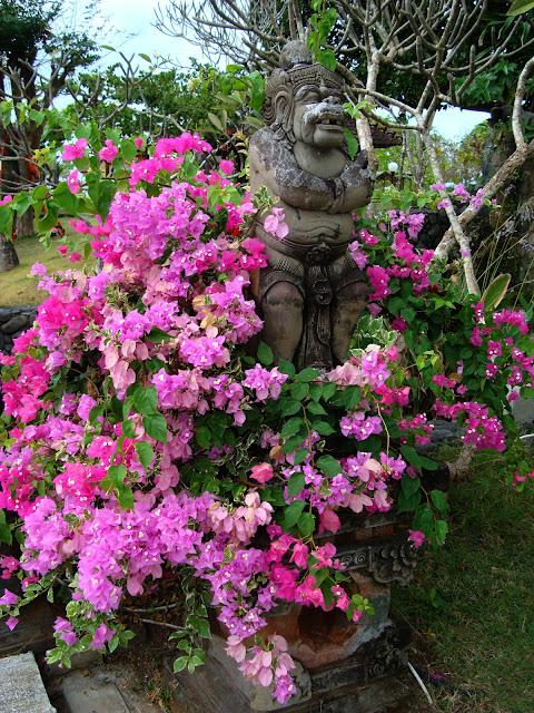 Изображение скульптуры божества среди цветов