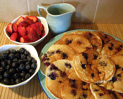 Platter of blueberry pancakes, blueberries, strawberries, and maple syrup