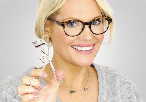 chica con gafas y rizador de pestañas