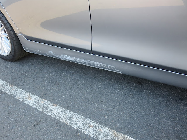 BMW with deep paint scratches on rocker panel before repairs at Almost Everything Auto Body