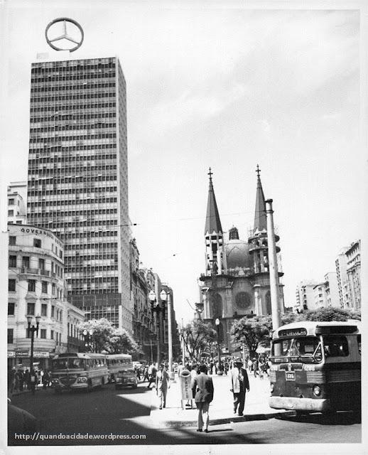 Fotografia antiga da Praça da Sé, com ônibus, a catedral, e um edifício com propaganda da Mercedes-Bens, que foi demolido.