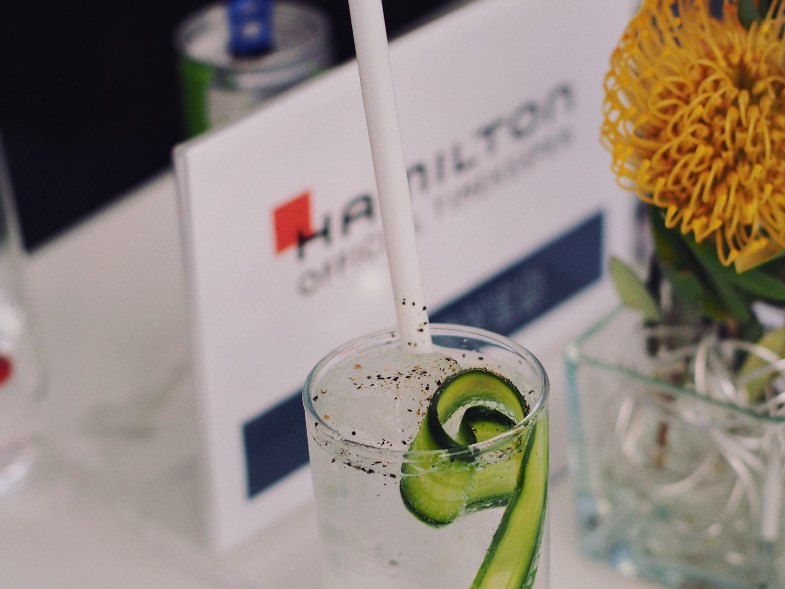 Ein Glas Gin Tonic vor einem Hamilton Schild