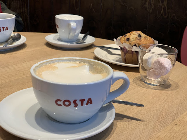 A table in Costa with a number of mugs and Blueberry Muffin on