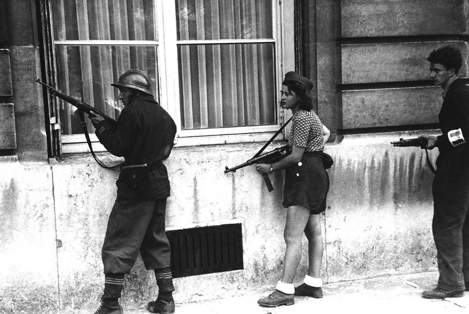 A girl of the resistance movement is a member of a patrol to rout out the Germans snipers still left in areas in Paris, France, on August 29, 1944. The girl had killed two Germans in the Paris Fighting two days previously.