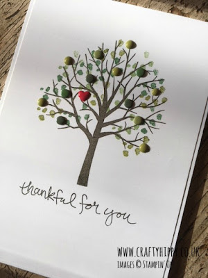 A picture of a greetings card made on White Cardstock depicting a tree made with the Sheltering Tree stamp set by Stampin' Up! It has green leaves and a red heart.