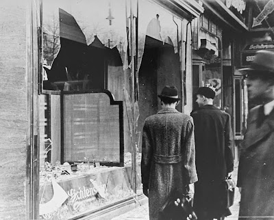 Germans pass by the broken shop window of a Jewish-owned business that was destroyed during Kristallnacht.