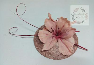 tocado con base de sinamay trenzada en color nude con flor pintada en nude y granate y raquis de plumas en granate