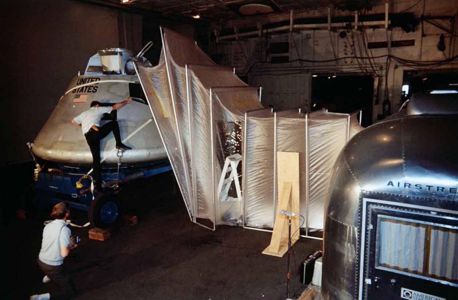 Man climbing at the Apollo Command Module inside the Mobile Quarantine Facility.