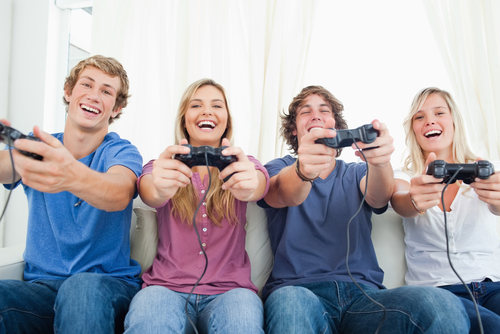 A group playing video games and smiling as they all look into the camera