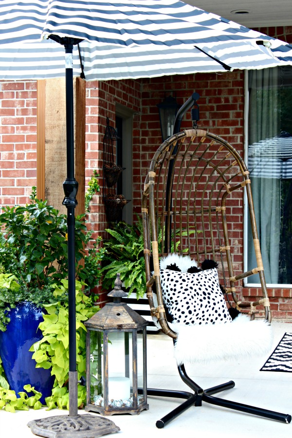 hanging swing chair, black and white striped umbrella, lantern, outdoor living area