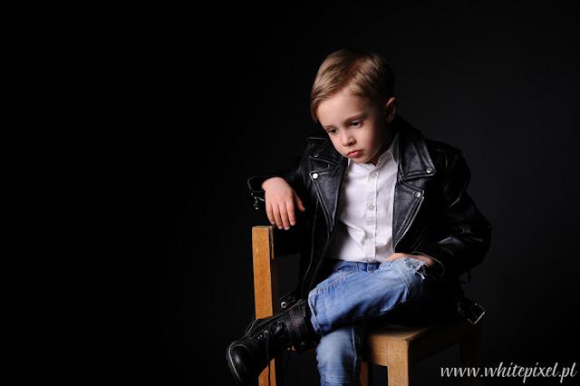 smutny chłopiec na czarnym tle pozuje do katalogu