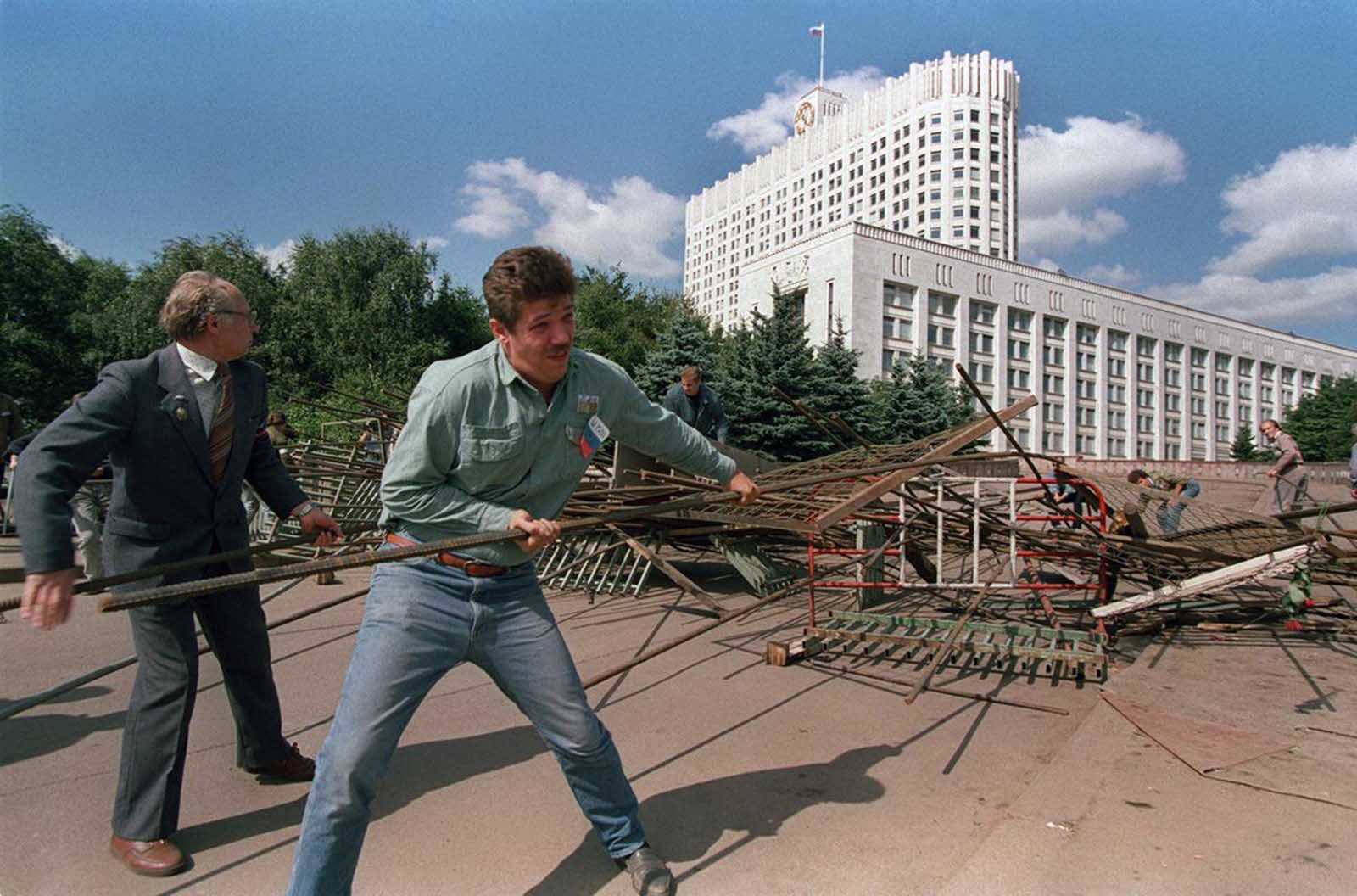 A group of Boris Yeltsin supporters rip apart one of the barricades surrounding the Russian federation building in Moscow, on August 25, 1991, following a coup attempt a few days before that eventually failed.