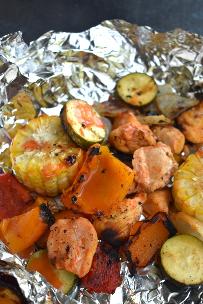 Buffalo Chicken Foil Packets is the perfect meal to make on the grill with spicy buffalo chicken, corn on the cob, bell peppers, onions and zucchini. www.nutritionistreviews.com