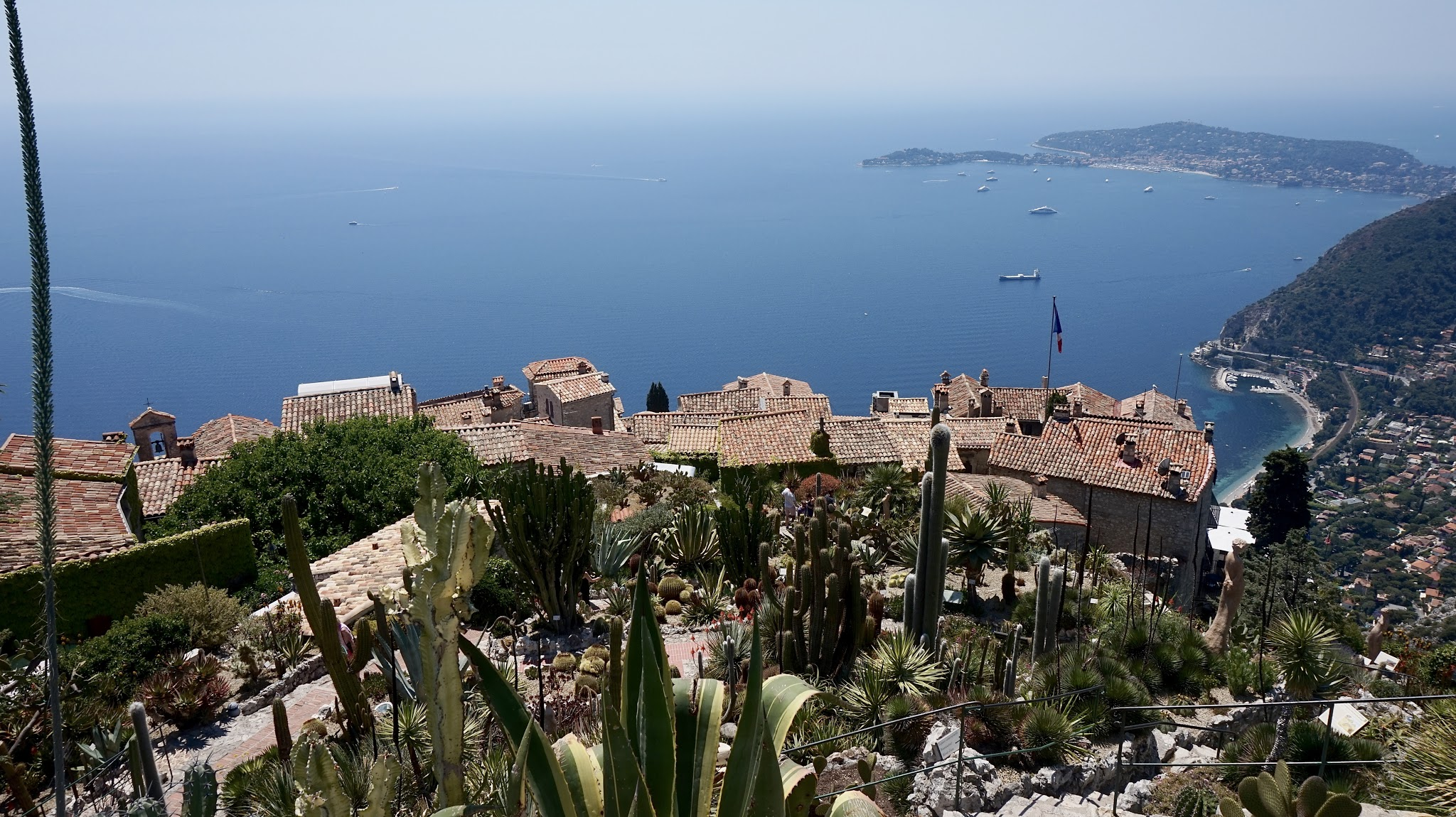 view from atop the high cliff in Eze, looking down to a blue sea, with red rooftops and exotic plants