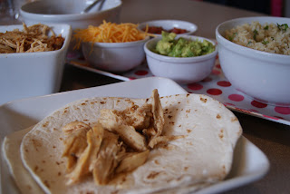 A single flour tortilla, topped with shredded chicken, along side of shredded cheese, guacamole, and shredded chicken all in bowls along side of the tortilla on a white plate.