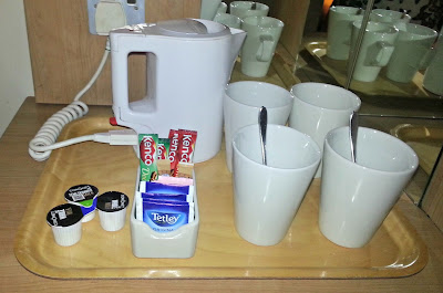 Kettle, mugs, tea bags, milk cartons, etc, on tray.