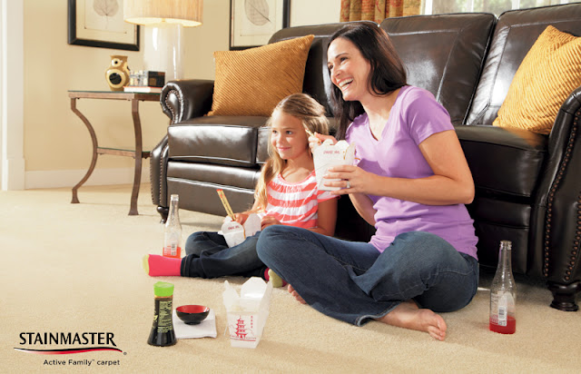 A mom and daughter eat on the carpet during movie night.