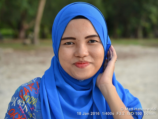 Matt Hahnewald Photography; Facing the World; closeup; street portrait; headshot; outdoor; Asia; Southeast Asia; Malaysia; Langkawi; Kuah; smiling; Malay woman; blue hijab; posing; beach; stylish; 1Malaysia; travel; travel destination; Muslima; Islam; eye contact; closed-mouth smile