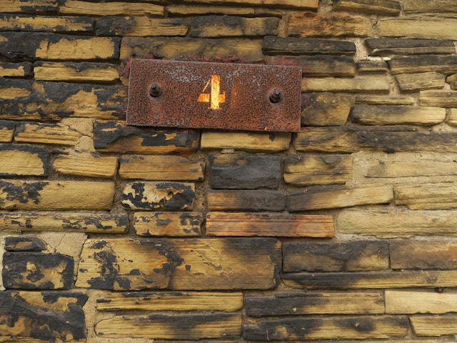 Rusting metal plate with 4 printed on it fixed to tall stone wall.