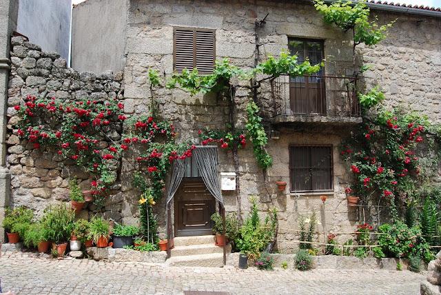 Preciosa fachada de piedra llena de plantas y flores en el pueblo de Monsanto