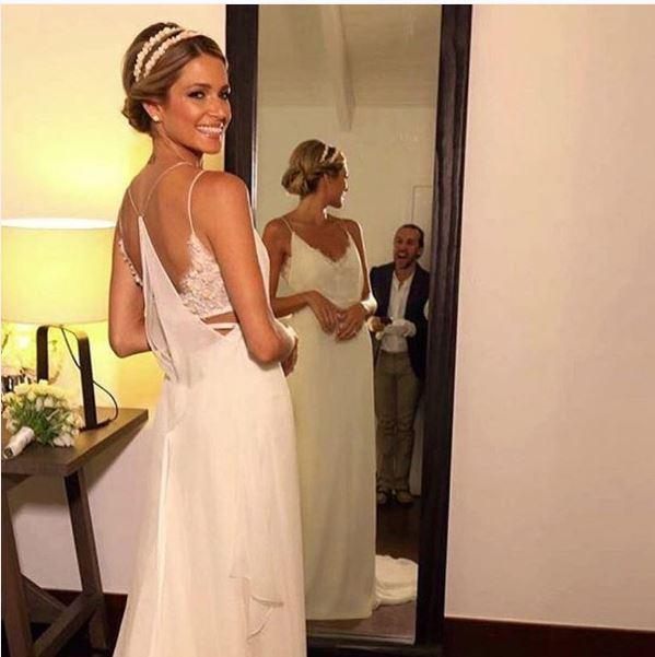 Helena Bourdon de noiva em frente ao espelho olhando para trás