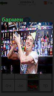 Около барной стойки бармен работает с фужером на голове