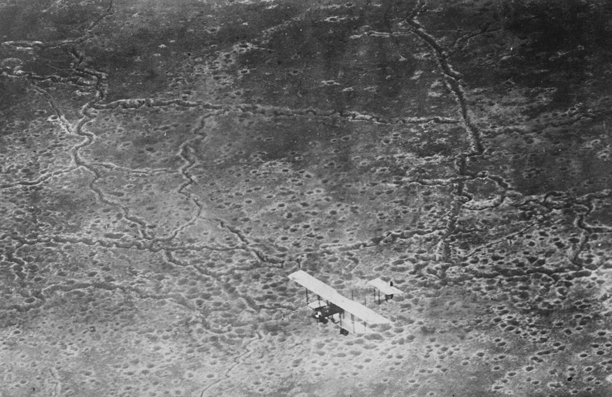 Un avión vuela sobre tierra de nadie, un campo de batalla europeo destruido por bombas y excavadores de trincheras.