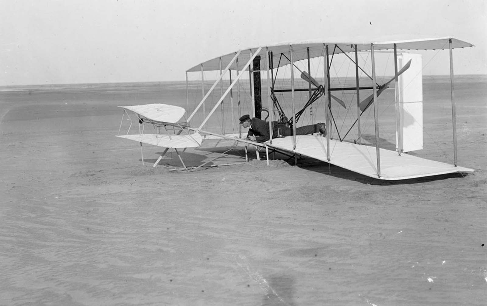 Wilbur Wright at the controls of the damaged Wright Flyer, on the ground after an unsuccessful trial on December 14, 1903, in Kitty Hawk, North Carolina.