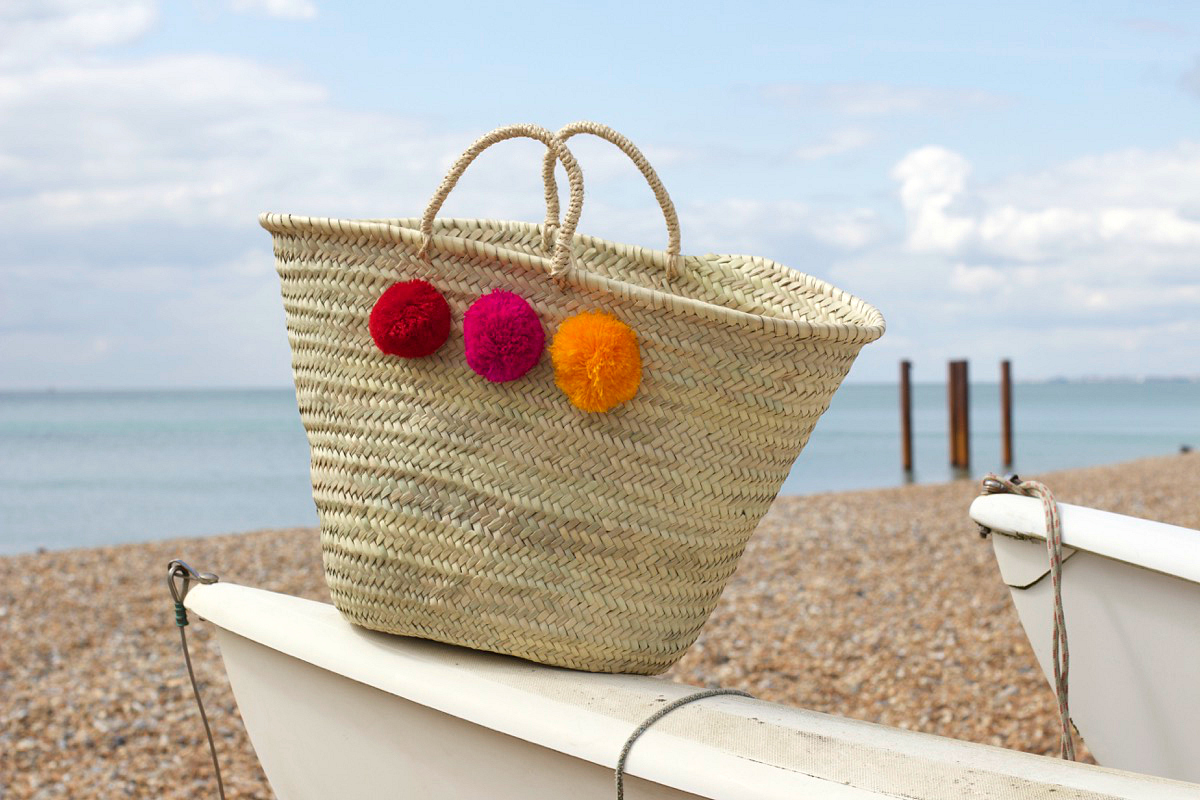 a beachside favourite, the moroccan pom pom woven basket bag from postcards home