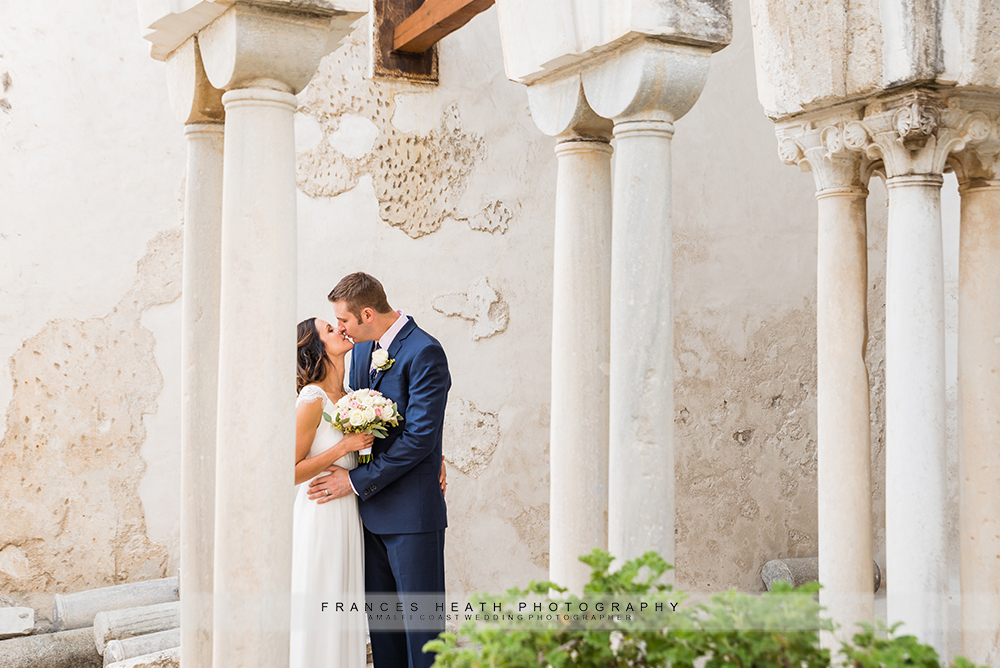 Bride and groom kissing in Amalfi cloisters