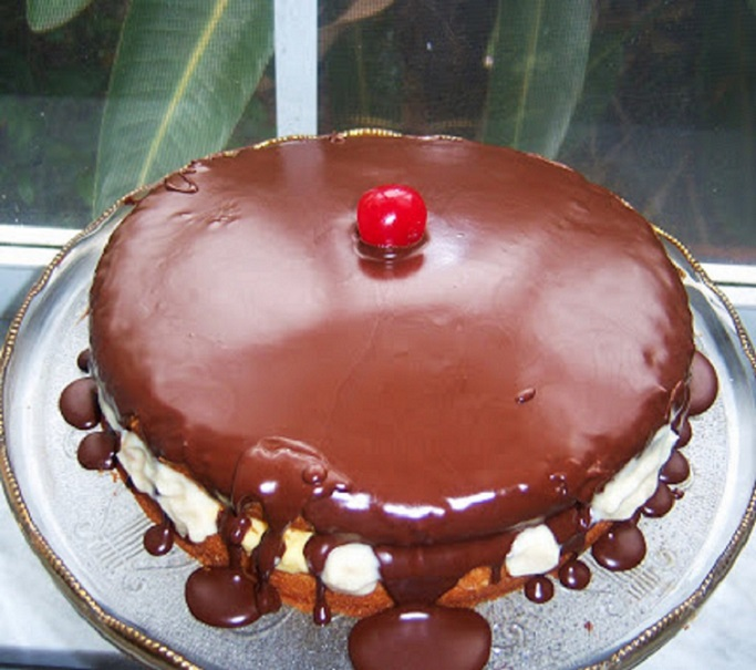 Rich golden cake with Italian pastry cream filling and chocolate ganache on top on a pedestal cake dish with a cherry in the middle of the cake