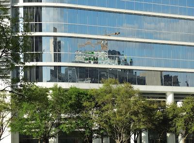 Reflection of crane atop the SkyHouse II in the glass facade of Chevron Skyscraper