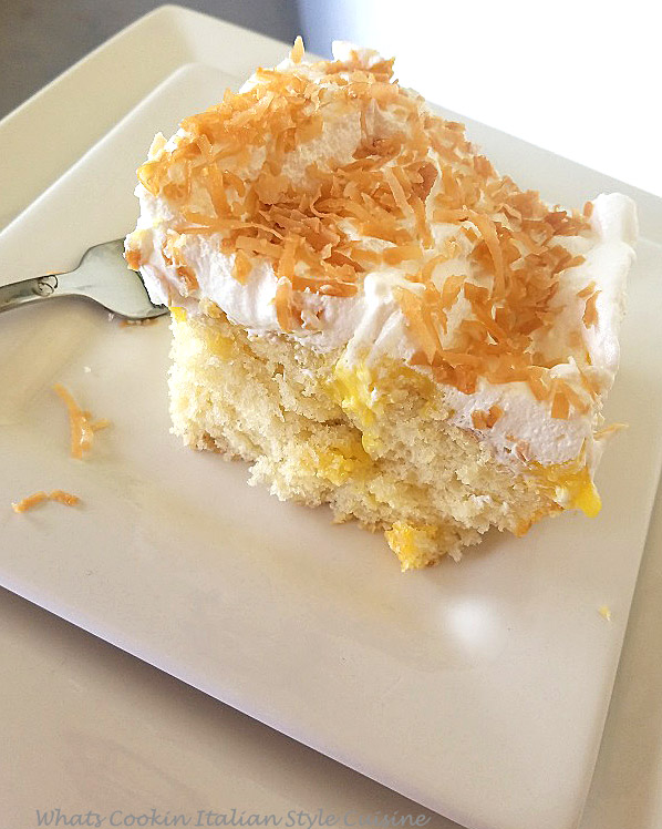 This is a  slice of coconut cake with coconut cream pudding that is called poke cakes because you poke holes in the cakes and the coconut cream pudding is throughout the cake then piled high with whipped cream and toasted coconut on top