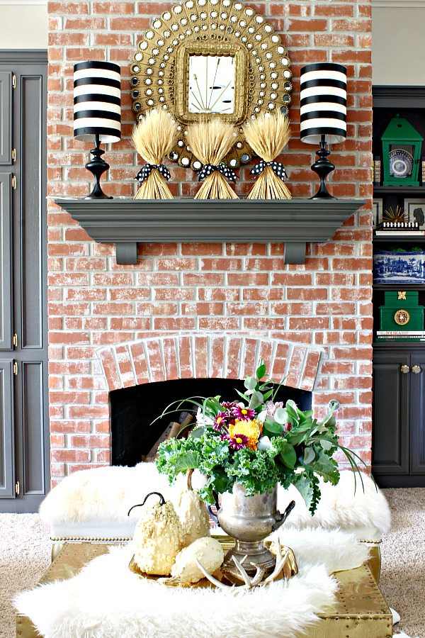 peacock mirror, striped lampshades, faux fur, stacked logs, brick fireplace, fresh flowers, vintage silver urn