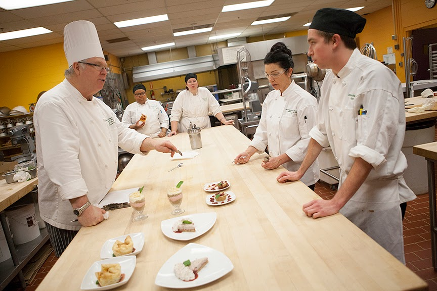 Chef Vern Wolfram, left, and his assistant, Patricia Massey, right, critique Joe Kaufman, far right, on his dessert. (Photo by Philip Hall/University of Alaska Anchorage)