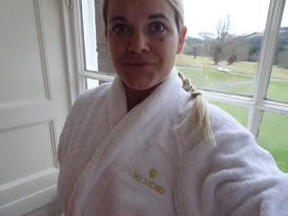 blonde woman in white stobo robe in front of huge window with grass in background