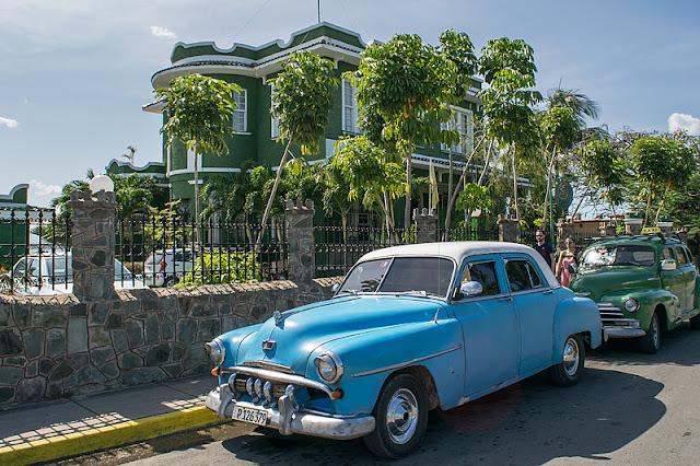 Vieilles voitures américaines stationnées devant un palais dans Punta Gorda