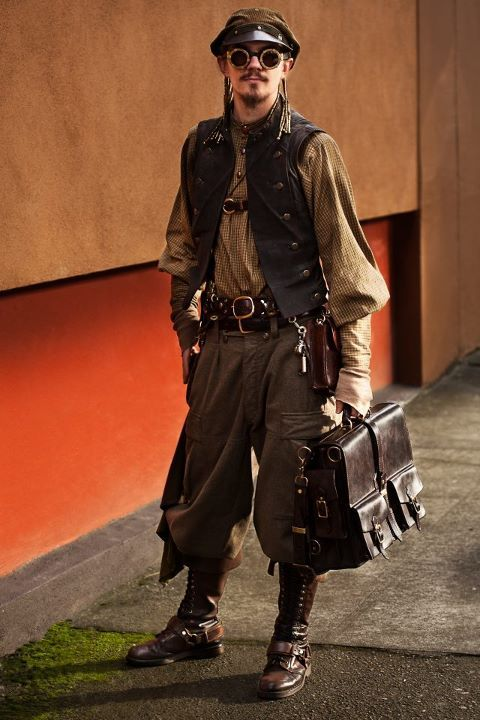 Steampunk man in working class laborer clothing. He wears trousers, a hat, goggles, vest, shirt, boots and carries a leather satchel. Men's working class steampunk clothing and fashion from the victorian era.