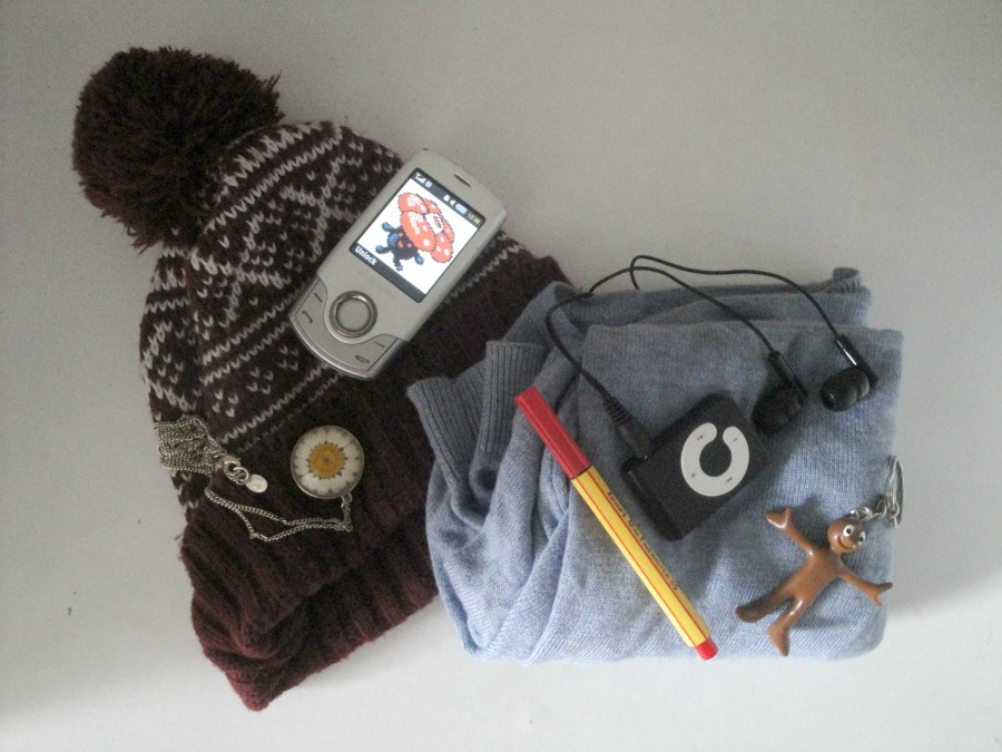 A collection of items including a folded blue cardigan, a red woolly hat, an mp3 player, phone, necklace, and pen.