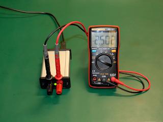 Tensão de saída da fonte a ser medida com um multímetro. A tensão está definida para 2,5V.
