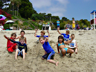 Group of young children playing together on the beach at Aloha Beach Camp's Paradise Cove summer camp program in Los Angeles, CA